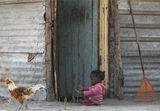 Playing Outside, Okavango Delta, Botswana, Africa, village, girl, sitting, dust, sand, fingers, engrossed, tin shack, ro photo