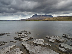 Jig-saw puzzle pieces of eroded rock provide a foreground for Ardvreck Castle on a gloomy Spring day at Loch Assynt and the brooding hulk of the Quinag behind