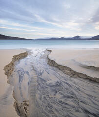 Fabulous beach carvings etched by the flow of a peat stream cutting its way through wet sand to the sea on Traigh Rosamol in Harris