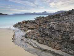 A peat stream cuts a scalloped channel around gneiss cliffs at the northern end of Traigh Rosamol beach on Harris.