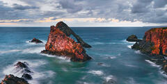 Red sunset light turns the Bowfiddle rock stack and cliffs at Portknockie on the Moray coast the colour of blood.