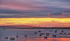 Sunset at the Findhorn estuary above the moored boats at high tide and sunset with the Moray Firth beyond.