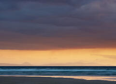 A distant view across the Moray Firth at sunrise with the mountains etched against an apricot sky.