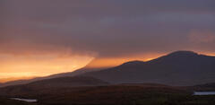 Caramel coloured beams of light broke through storm clouds above the Inverpolly peaks near Knockan Crag.