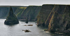 A long shot employing perspective compression of the impressive dagger like sea stacks at Duncansby Head with two folk on the cliffs providing scale.