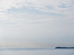 An army of wind turbines peers through a veil of mist near the harbour town of keiss on the east coast of Caithness on a windless summer evening.