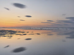 Soft glowing colours of orange and blue reflected in smooth water at Findhorn Bay, Moray, Scotland