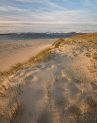 Ancient footprints on top of a sand dune at Scarista have filled in to become dimples in soft sand at sunset.