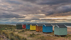 Gaps in the low lying clouds behind the beach huts at Findhorn bay let through a fan of crespuscular rays shortly before sunset.