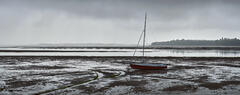 Monochromatic light and a breaking storm over the Findhorn estuary with the Gandy Goose dinghy marooned on the foreshore offering a small splash of colour.
