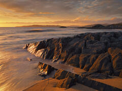 Rock caramelised by the setting sun and a sea turned to gold at Traigh Mhor on Harris.