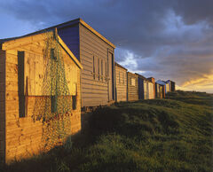 Hopemans colourful beach huts meander along the sea front and gleam with golden light at sunset.