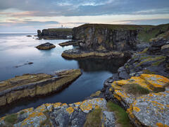 A shapely cove with intersecting textures of colourful rock encrusted with lichen and the Noss Head lighthouse standing proud on the Caithness cliff top.