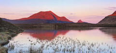 Ruby coloured sunlight strikes the mountain peaks of Stac pollaidh, Cul Beag and Cul Mor shortly after sunrise across Loch an Ais.