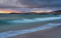 An inky black sky temporarily parts to allow a tangerine streak of sunrise light to strike the peaks behind the evocatively named and beautiful Mellon Udrigle.