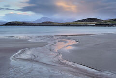 A Z-shaped peat stream discherging into the sea at Mellon Udrigle is stained pink by the reflected light of sunlit clouds illuminated by the setting sun.