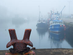 A sea haar rolls in over Burghead harbour on the Moray coast with the ghostly apparitions of old trawler boats moored at the quayside beyond the iron rope claw.