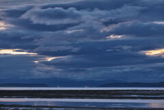 Distant oil rigs turn their lights on and glow in the twilight blue of early evening towards Inverness on the Moray Firth from Findhorn.