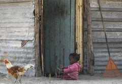 Playing Outside, Okavango Delta, Botswana, Africa, village, girl, sitting, dust, sand, fingers, engrossed, tin shack, ro