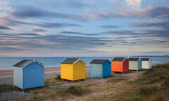 A colourful collection of expensive beach huts at sunset beside the dunes at Findhorn Bay on the Moray coast.
