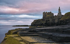 A rosy glow to the clouds shortly after a gloomy sunset at Castle Girnigoe and Sinclair near Noss Head on the Caithness coast.