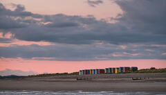 Summer Solstice sunrise greets the day with a pinkening sky above the rainbow coloured Findhorn beach huts.