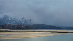 fleeting sunlight and squally snow showers combine in a moment of transient light over the Tongue estuary and the Ben Loyal mountain peaks