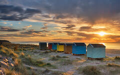 Sunlight from the setting sun filters through the gaps between the rainbow coloured beach huts at Findhorn Bay on the Moray coast.