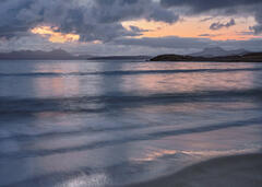 Rolling waves wash up onto mellon Udrigles fine sandy beach at sunrise mixing a palette of tangerine and steely blue.