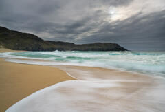 A surge of sea spume from a huge breaking wave rolls around my feet and creates a pleasing curve on the sandy beach at Dail Mhor on Lewis