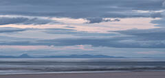 A blue tinged set of layered clouds floats above similarly coloured mountains on the other side of the Moray Firth just after sunset from Findhorn Bay.