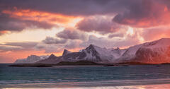 Sunrise reflected at Yttresand beach over the snow dusted peaks of Flakstaad  in Lofoten.