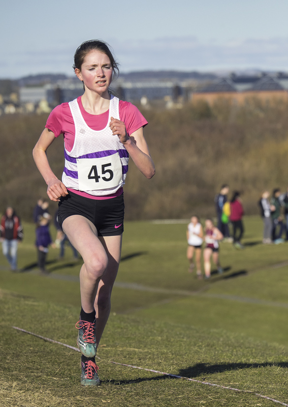 Anna MacFadyen of Forres Academy and Forres Harriers moves serenely into the lead on the second lap of the course eventually...