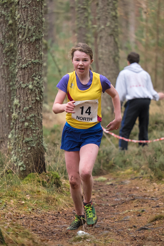Catriona Garvie emerges victorious from the woodland after a narrow tree root infested, muddy ascent to head for the finish line...