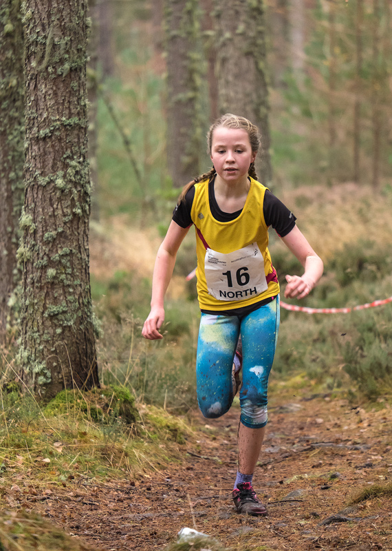 Silver medallist Kirsty Arnaud representing Inverness Harriers assists her team mate Catriona garvie in securing team gold in...
