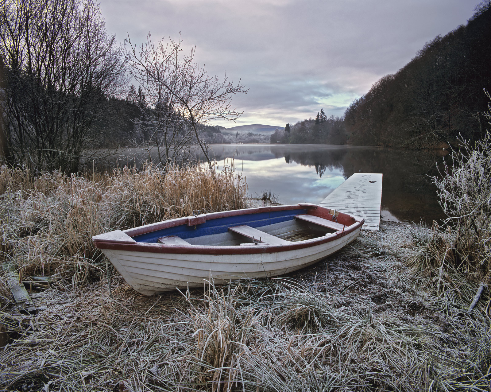 A fishing boat hauled out of the water at loch Ard in the depths of winter. It was immensely cold with a crisp frost covering...