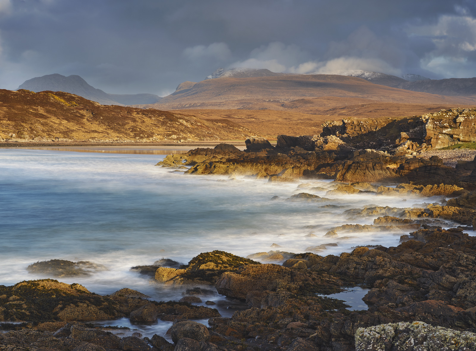 Rolling waves clatter the Achnahaird coast at sunset turning the hills to gold beneath a dark and squally sky.