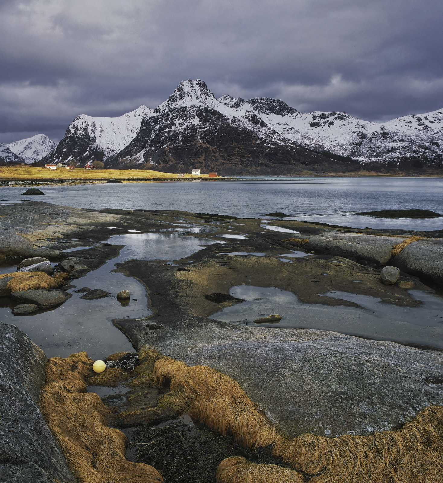 Snow capped mountains are the backdrop for Flakstad fjord and as the weather closes in and the sky turns to thunderous grey it...