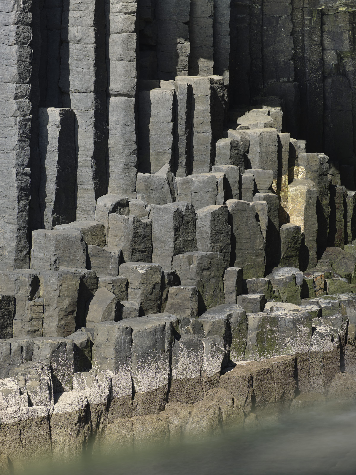 Surging sea and vertical columns of grey basalt are the main features of iconic Staffa island and here they are shown next to...
