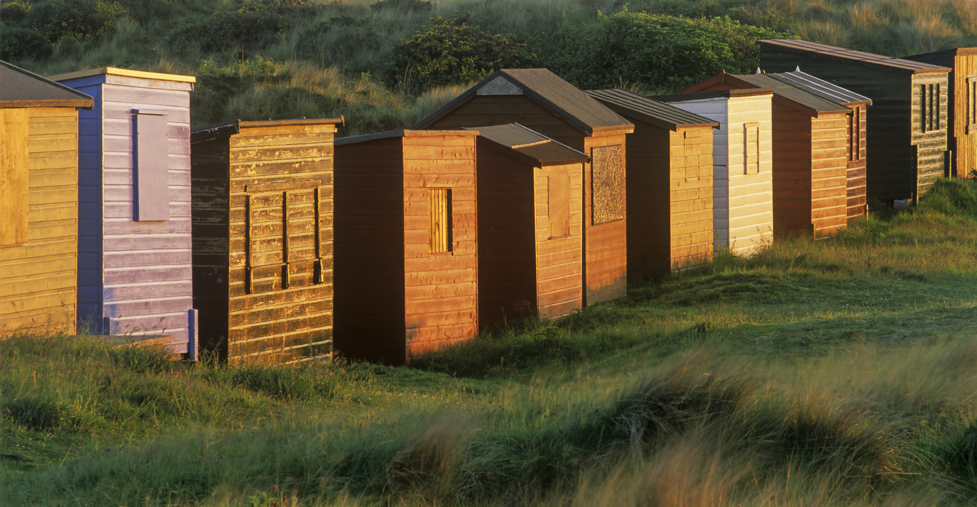 A row of beach huts reflects a setting sun at the edge of Hopeman bay forming an attractive line of golden facades along this...