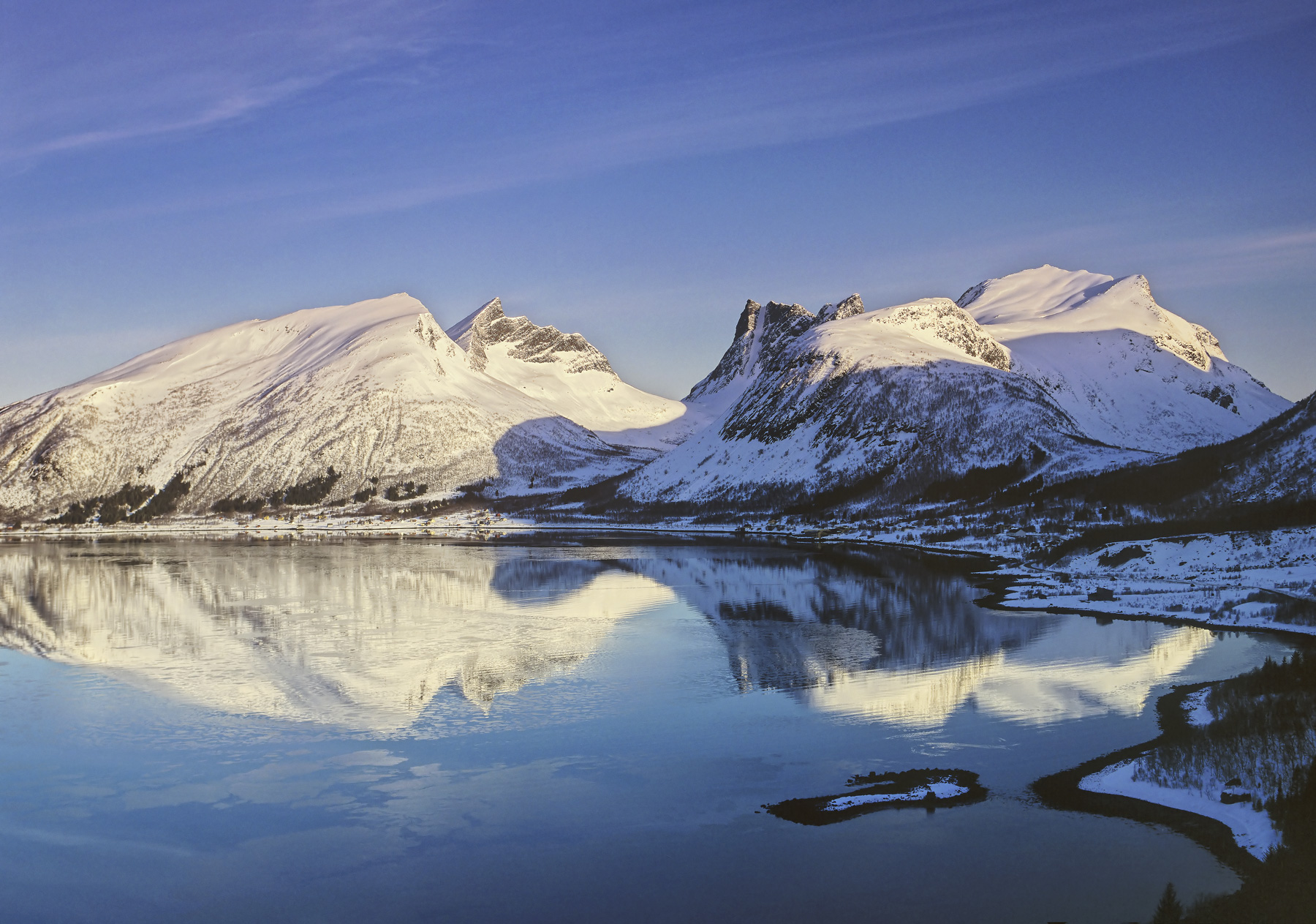 A fabulous reflection of the sunlit mountain peaks at the coast of Senja surrounding Bergsbotn bay taken shortly after sunrise...