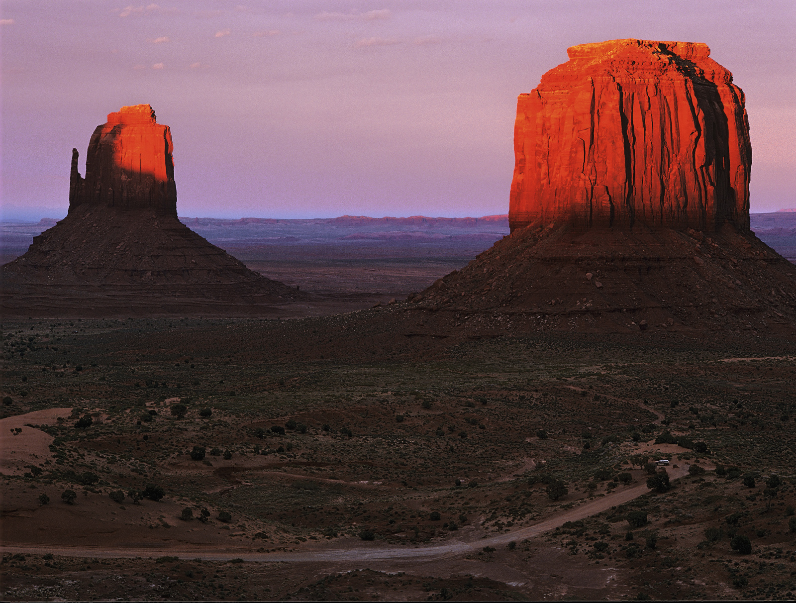 The two buttes turned scarlet courtesy of a letterbox thin gap on the horizon through which the setting sun obligingly passed...