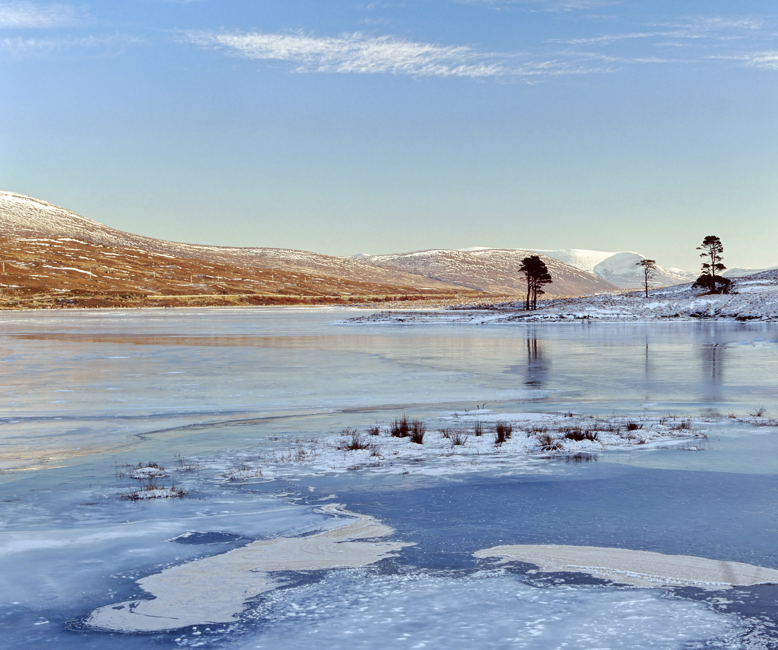 A crisp winters day and a laser blue sky high over a frozen loch reflects onto blue ice. This remote 1000 foot moorland...