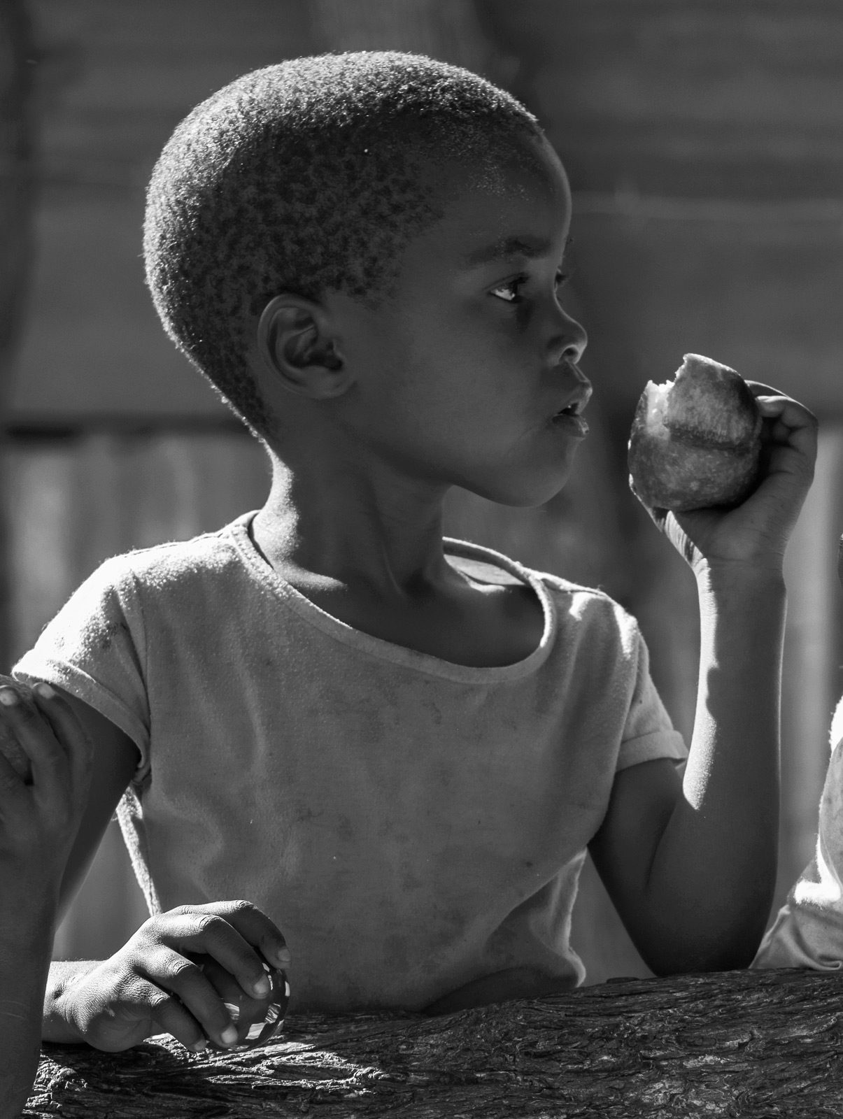 Gorgeous sharp African sunlight rim lights this wee girl munching on a deep fried doughnut outside her tin shack home. ...