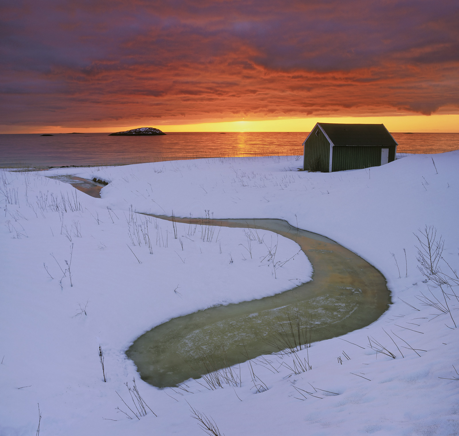 A meandering stream has all but been frozen over forming a Daliesque smear on the twilit blue snow beneath a sunset to die for...