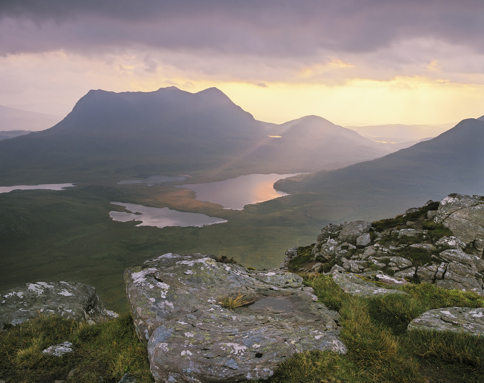 Standing on the summit of the Stac Pollaidh ridge top gazing out at the watery outline of Cul Mor and a breaking dawn on an early...
