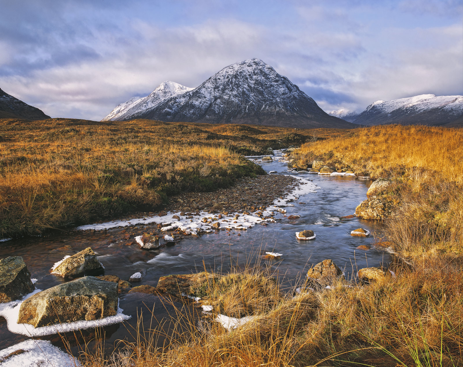 A rim of winter frost rings the rocks and the banks of a shallow tumbling stream that obligingly points to the pyramidial peak...