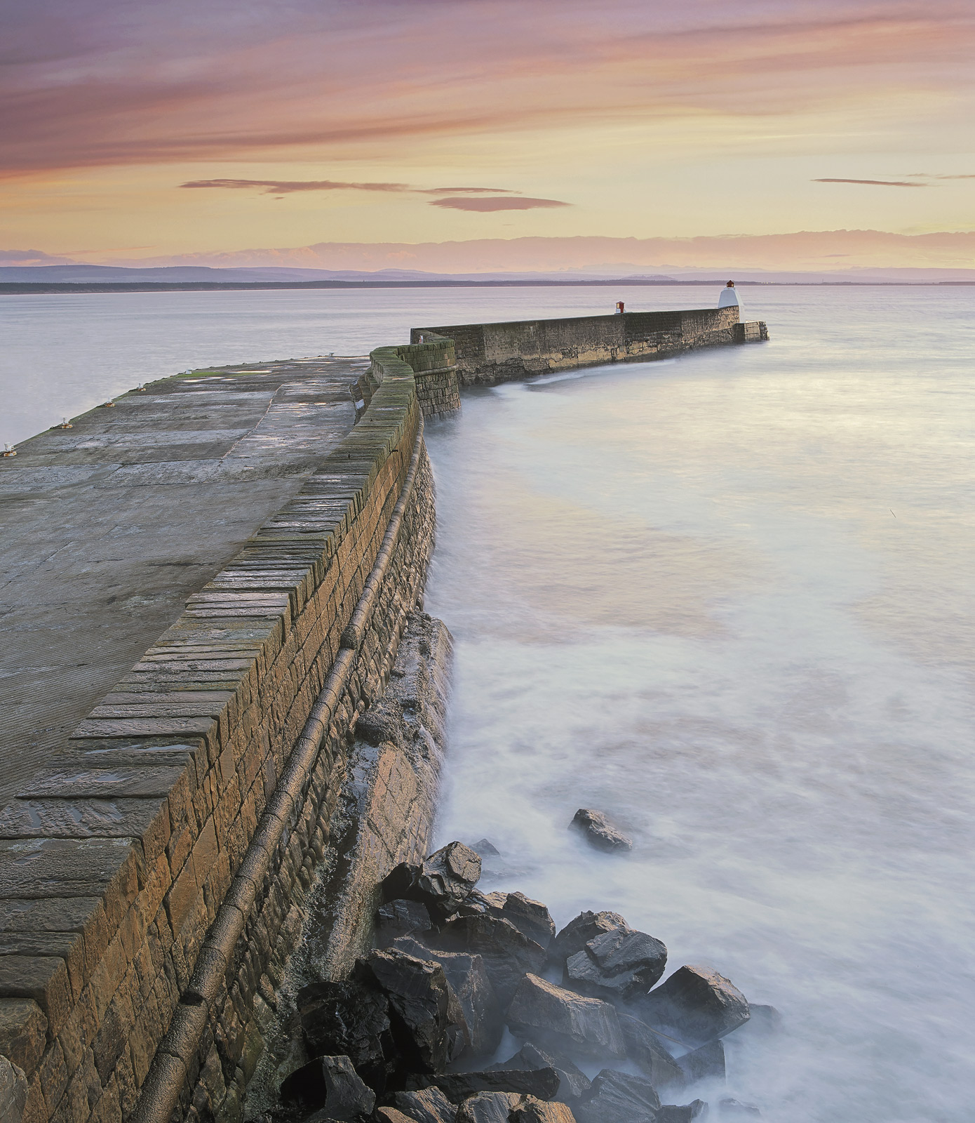 The curving flagstone harbour wall at Burghead stretches out across the turbulent waters of the Moray Firth on arough and...