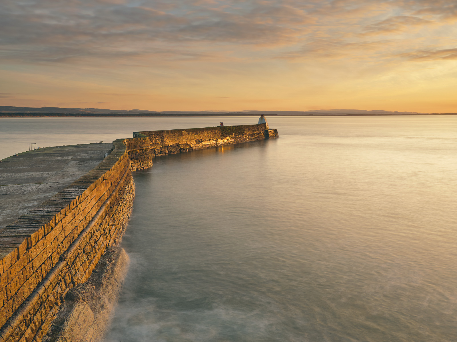 Golden sunlight strikes the sinuous line of the old stone harbour wall turning it a rich burnished gold.  The smooth sea had...