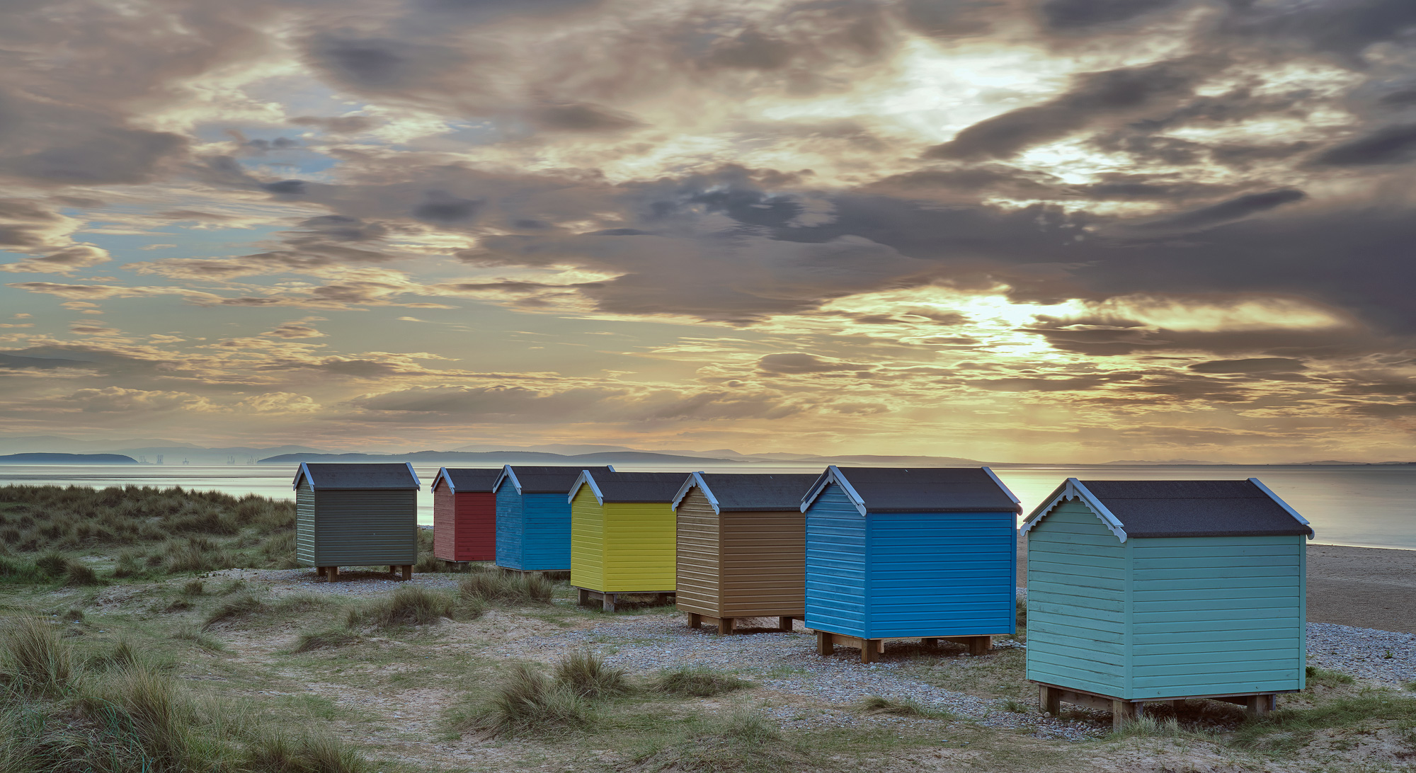 A Rainbow coloured set of beach huts is framed by a caramel sunset at Findhorn bay on the Moray coast.